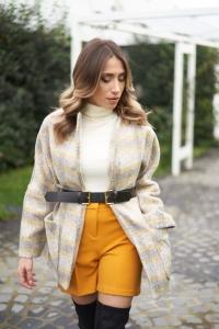 modella bionda che indossa un cappotto a quadri grigio e uno short giallo a vita alta